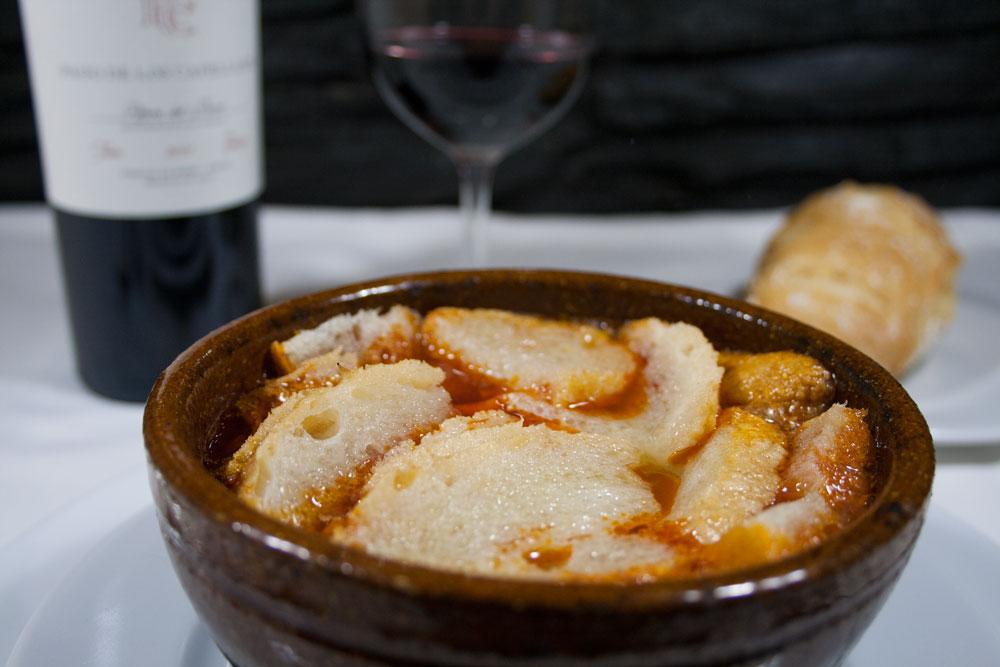 En bol de barro alto la sopa castellana con pan por encima