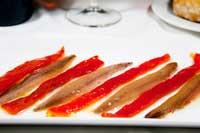 En plato alargado se sirven las anchoas de gran calibre junto a tiras de pimientos asados