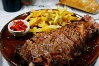 Chuletón cortado en tiras rodeado de patatas fritas y pimientos asados
