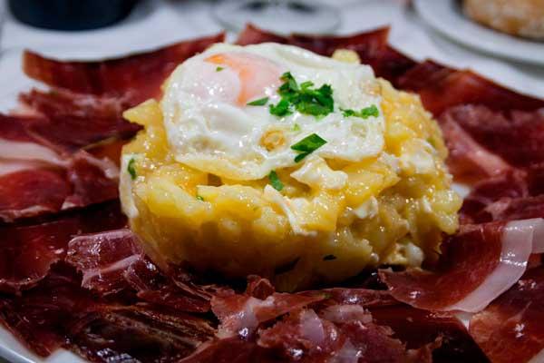 Sobre un lecho de jamón Ibérico de bellota un revuelto de huevos de corral