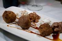 En bandeja largada tres bolas de leche frita acompañada de flores de nata y chocolate
