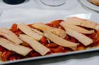 En un plato alargado y sobre un lecho de pimientos asados, tiras de ventresca de bonito