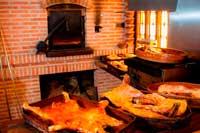 Delante del horno y sobre un mostrados dos cazuelas con cochinillo y cordero asados