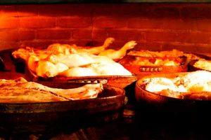 Pollos asandose en el horno de leña