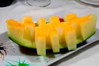 Sobre un plato adornado una raja de melón cortados en tiras