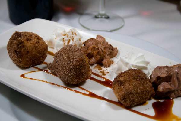 En plato alargado tres bolas de leche frita acompañadas de nata y chocolate en crema