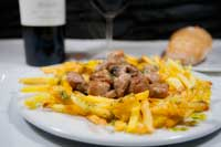 Primer plano de mollejas de cordero lechal sobre un lecho de patatas fritas